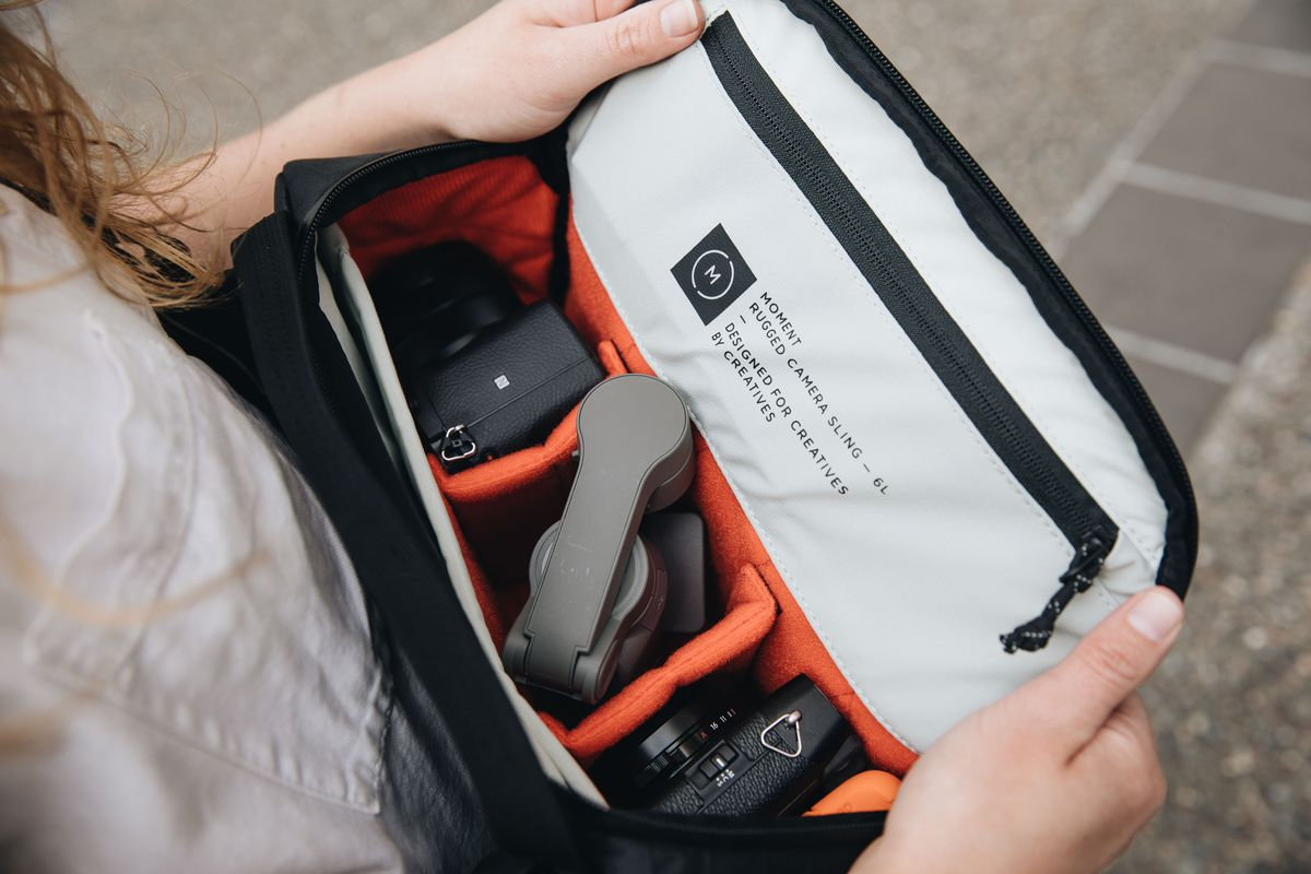 A Moment Rugged Camera Sling bag with its top open showing the interior.