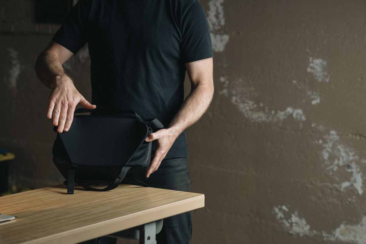 A man demonstrating the flexible, winged back panel of the Moment Rugged Camera Sling bag on a wooden table.