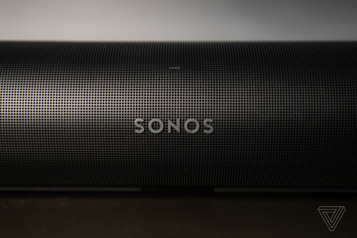A detail shot of the front of the Sonos Arc, showing the Sonos logo and many perforated holes in the outer casing.