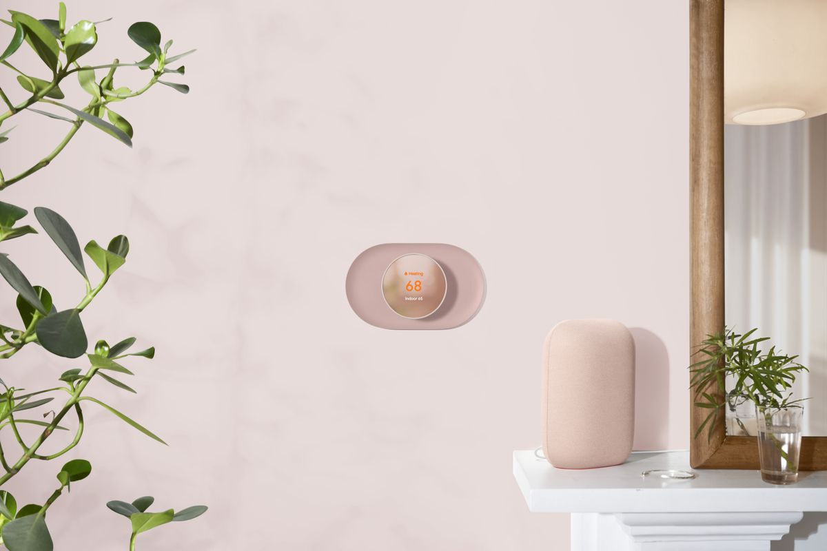 A light pink Nest Thermostat mounted on the wall with a matching color Nest Audio speaker on a shelf next to it.